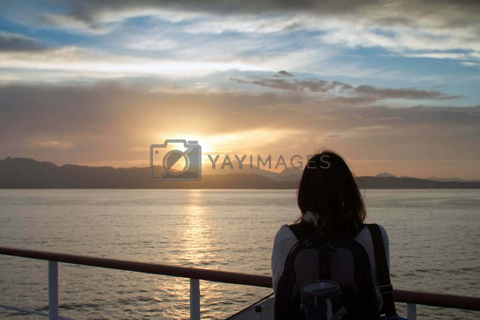 Young woman girl with backpack on shoulder shot from behind admires the sunrise on the Sardinian sea coast with intense orange coloring seen from the sea on the ferry that is about to dock