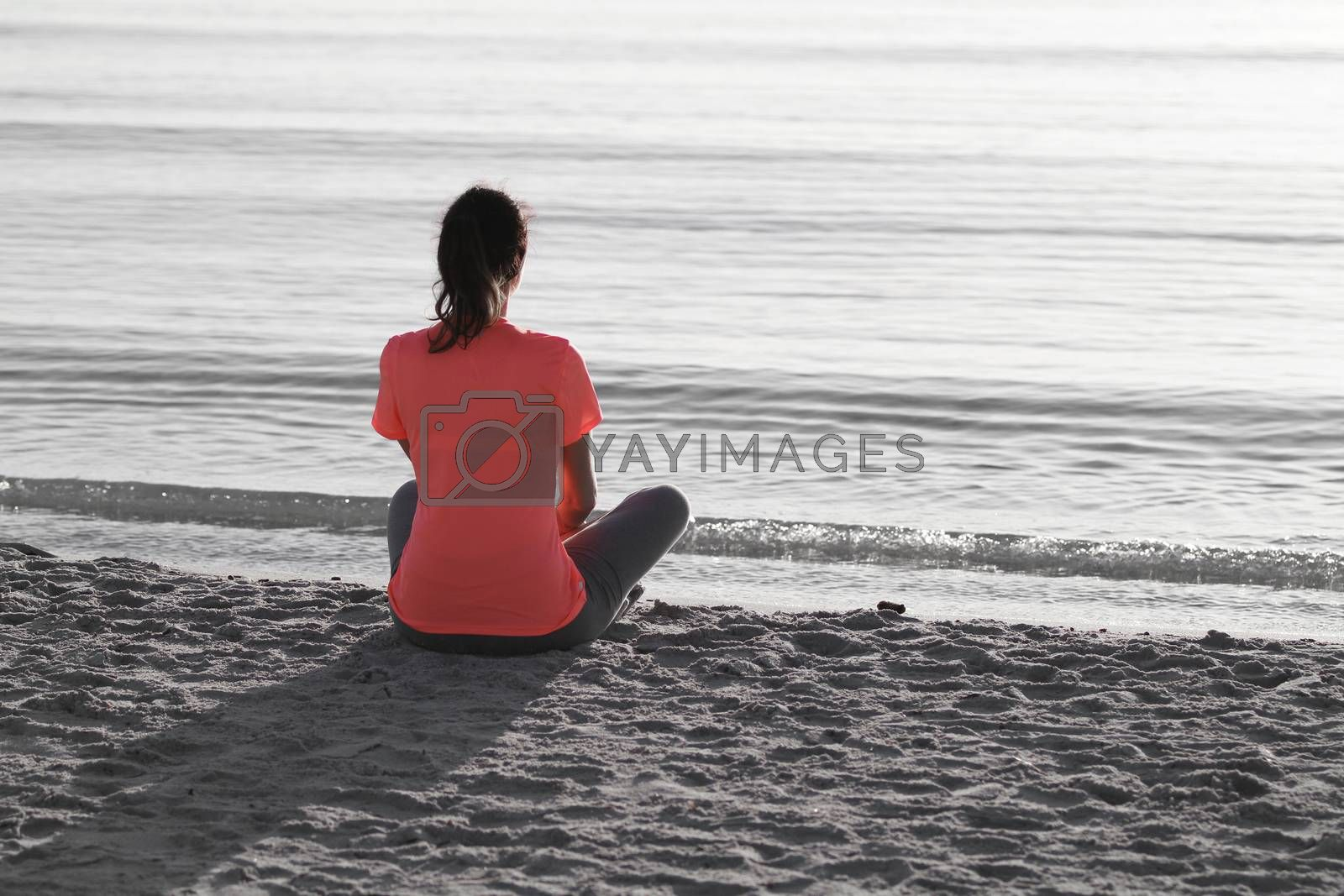 Young woman sitting on the shoreline of the sea at dawn in athle by robbyfontanesi