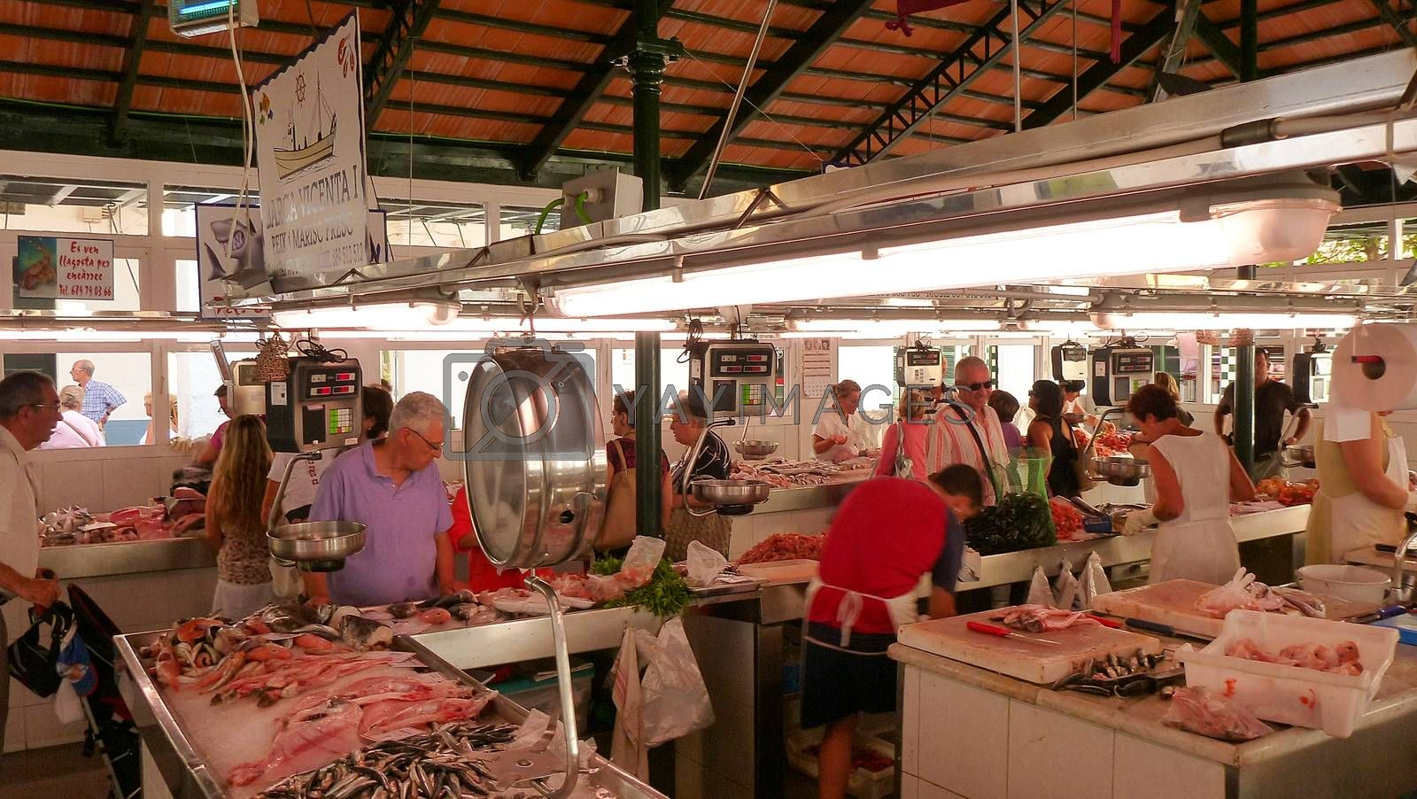 Menorca, Spain - june 28 - 2012 - View of the fish market in Ciutadella de Menorca, with various colorful fish for sale in the  foreground and tourist customers