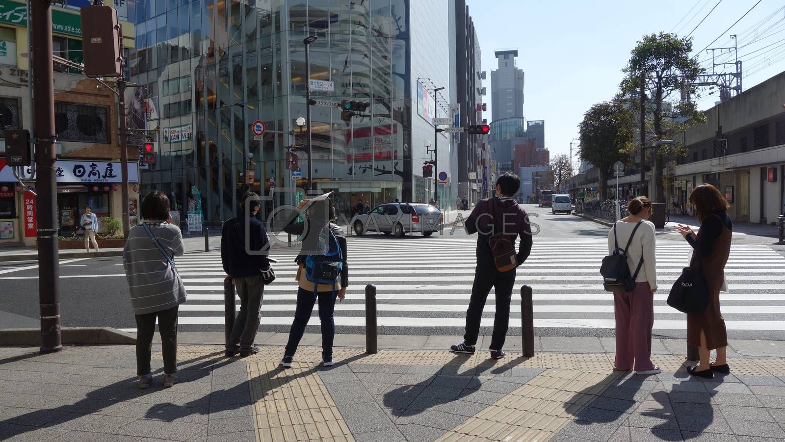 Tokyo, Japan - October 25, 2017 Tourist people with stand in front of crosswalk at the junction business street with car on the road (view from back)