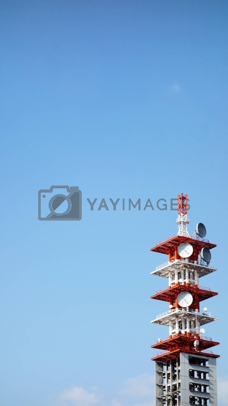 Telecommunication Tower in Tokyo, Japan . Cell Phone Signal Tower on blue sky background. Communication tower on blue sky. top of a cellular repeater tower. Cell tower white against a blue sky background. Copy space