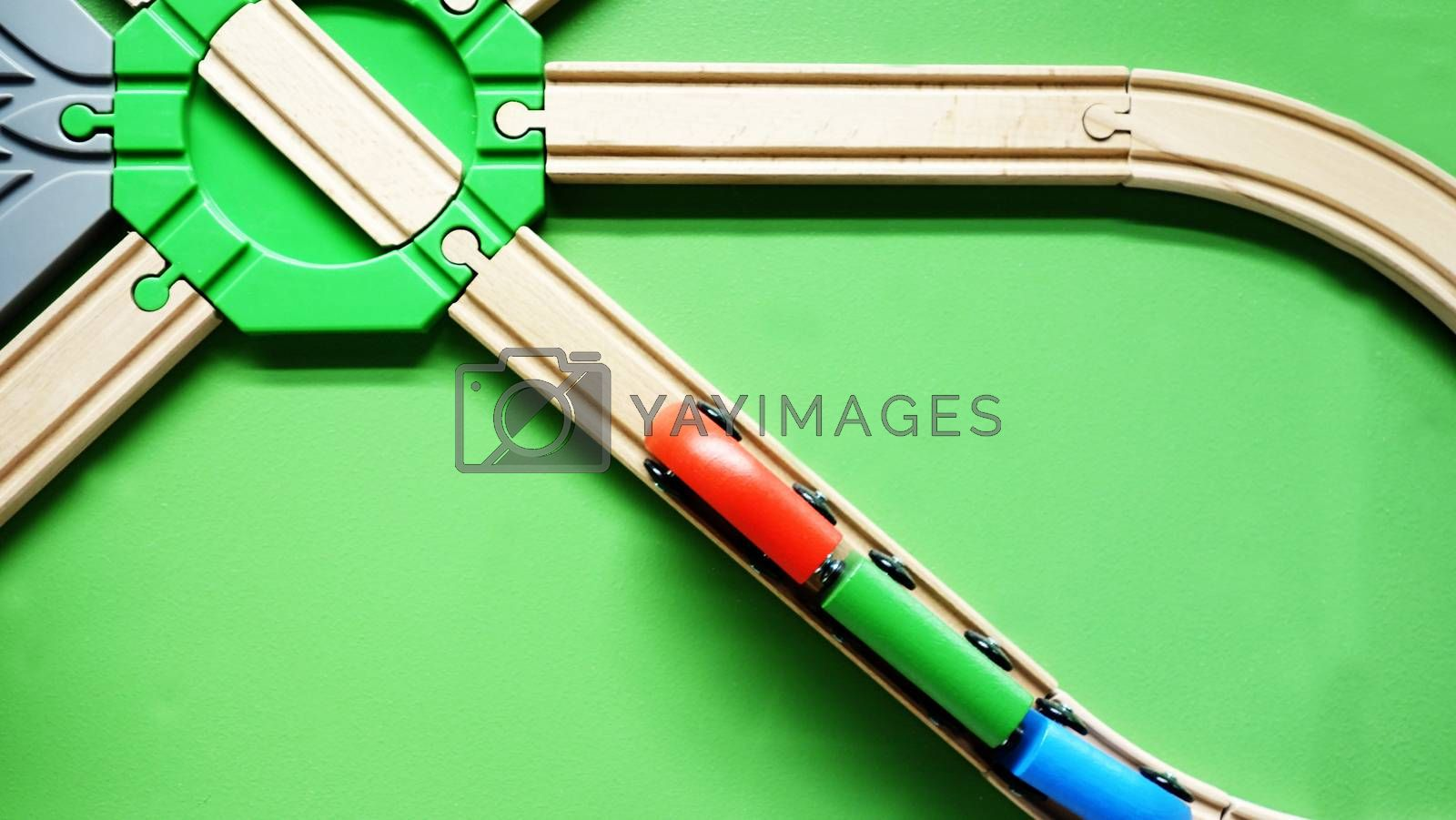 TOP VIEW: Wooden toy train move on curve wooden railways. Green background