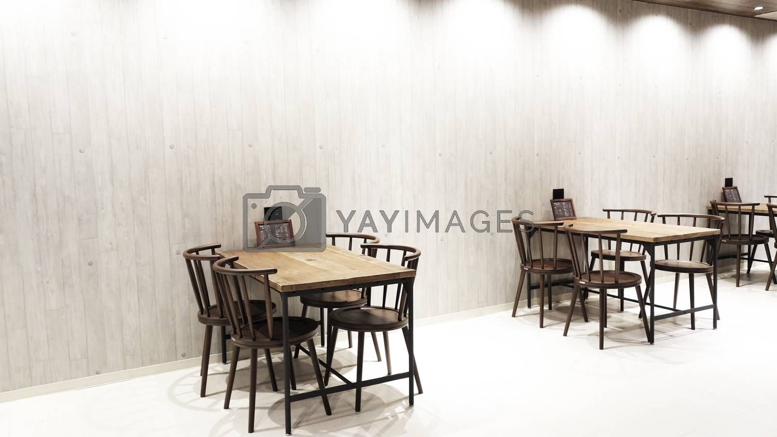 Wooden table and chair in the restaurant . Interior of restaurant food and beverage cafe with wooden table and chairs, food menu on the tabble and vintage wooden background.