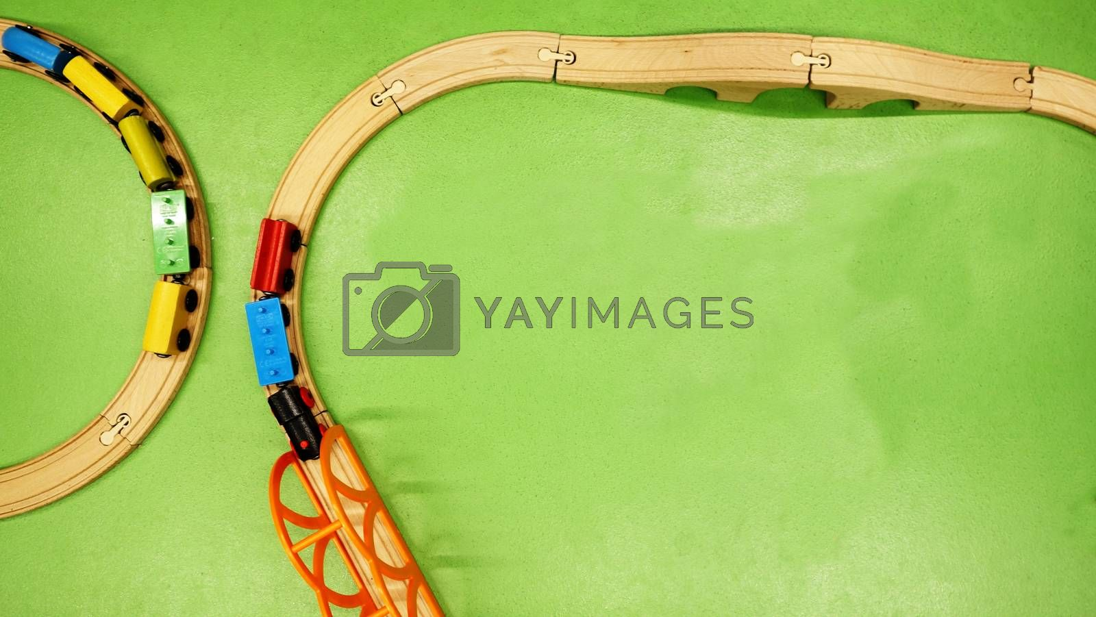 TOP VIEW: Wooden toy train on curve wooden railways with green background. Copy space for text