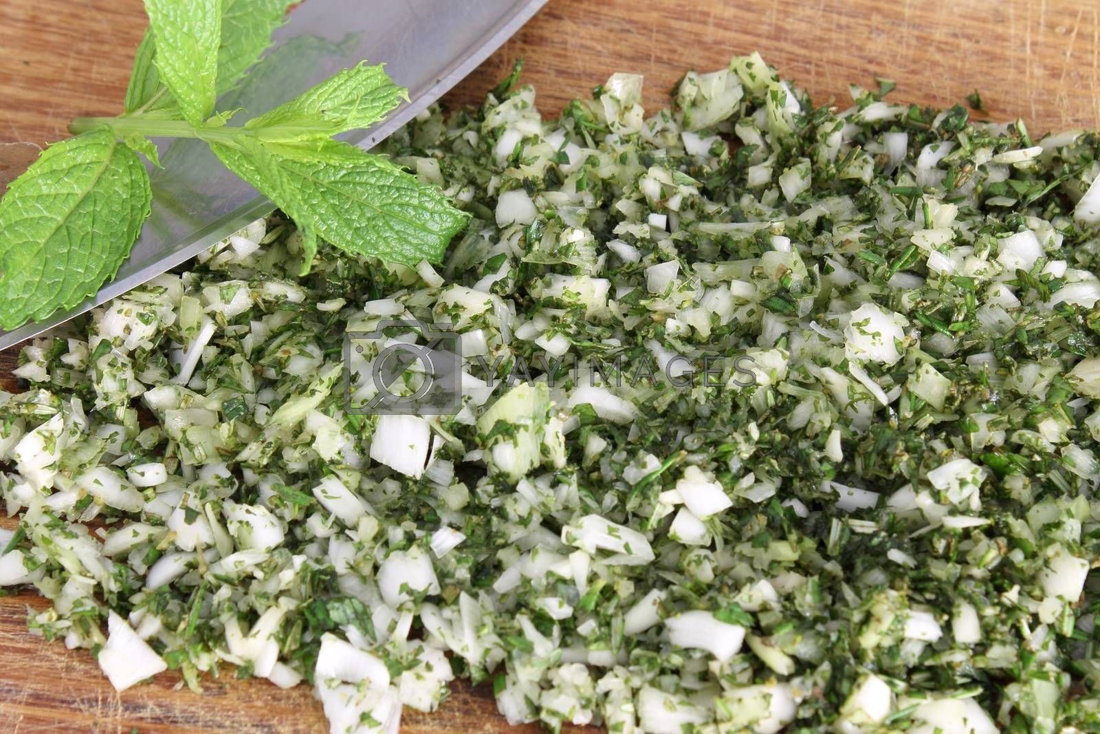 Chopped herbs and onion with mezzaluna