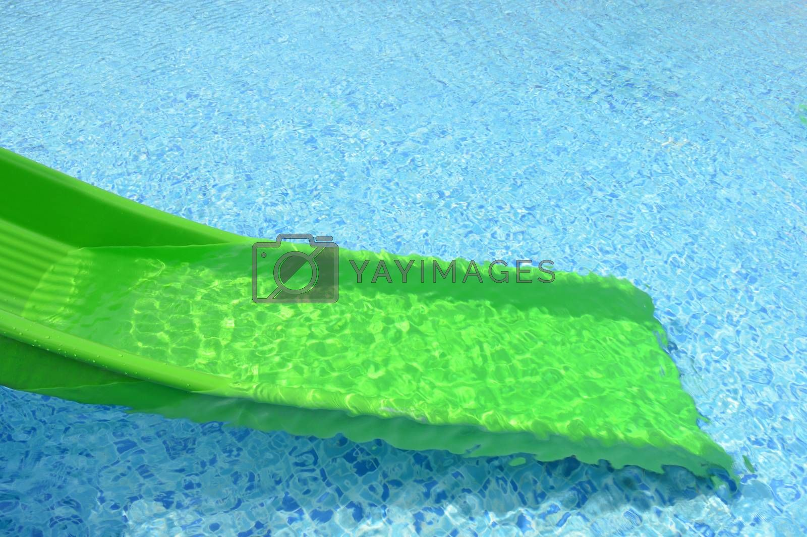 green plastic slider in front of swimming pool