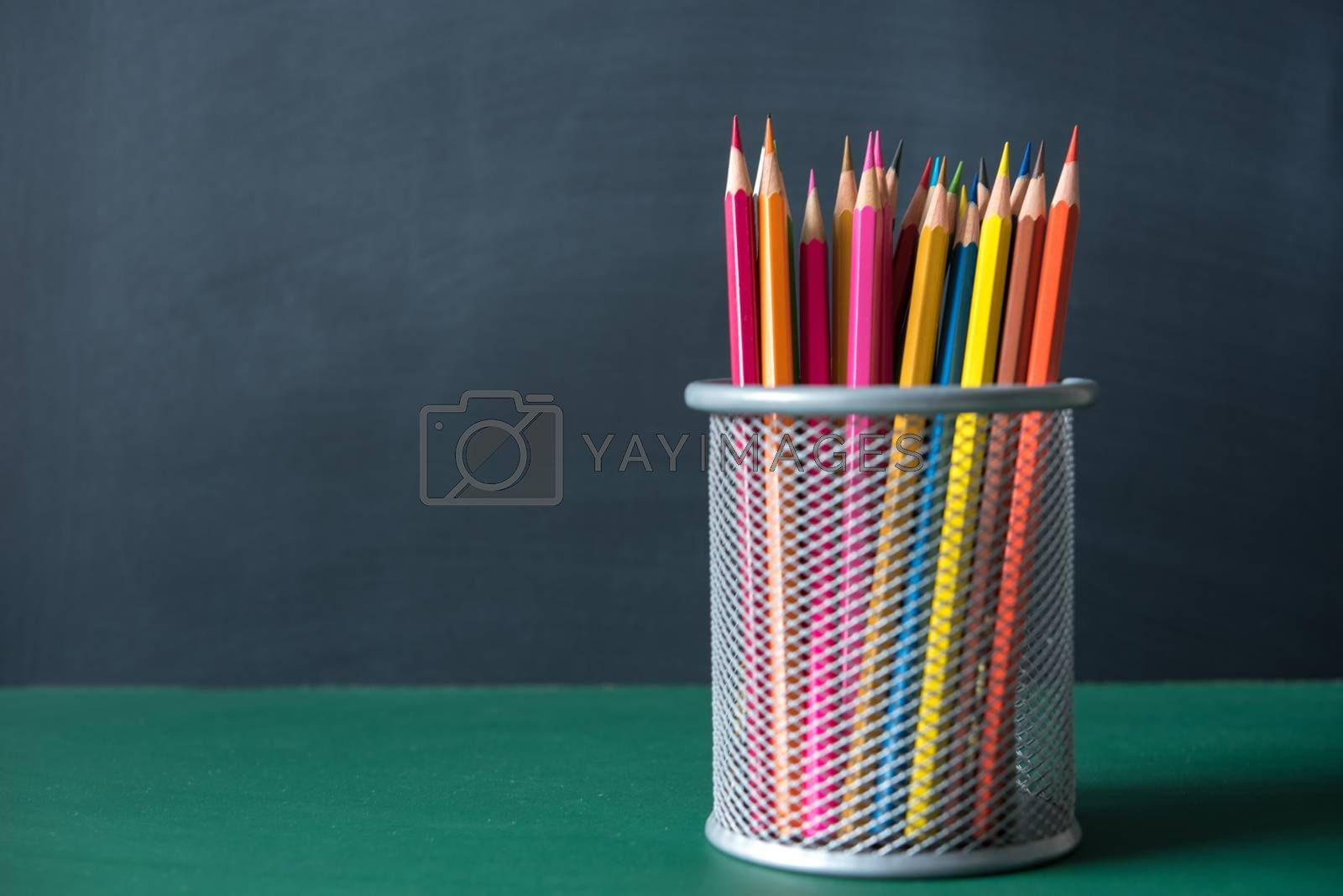 multicolor pencil in a box on black and green chalkboard backgro by Lerttanapunyaporn