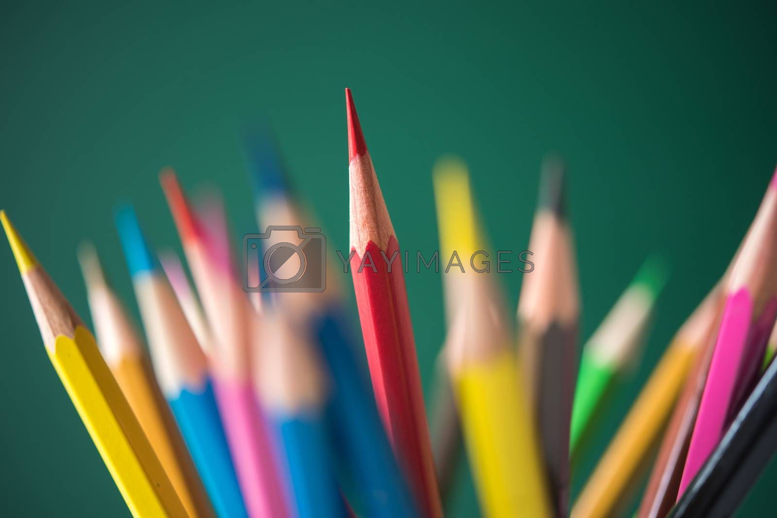 multicolor pencil on green chalkboard background by Lerttanapunyaporn
