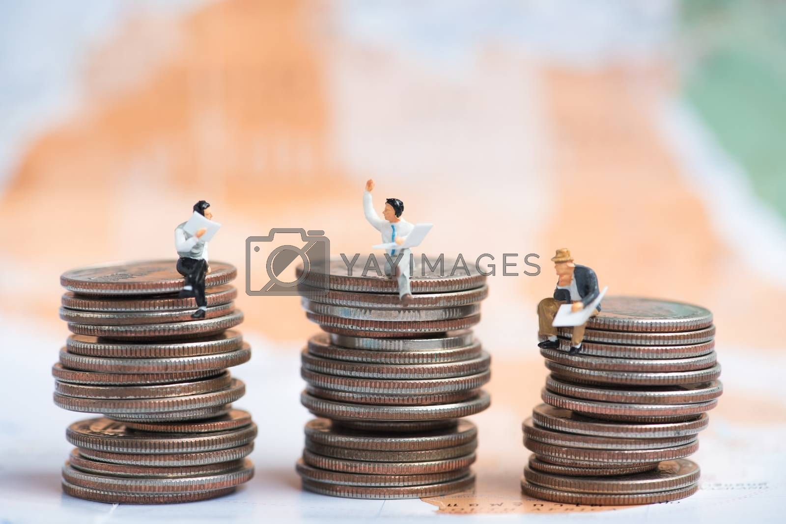 business miniature people sitting on stack of coins with blurred world map background.