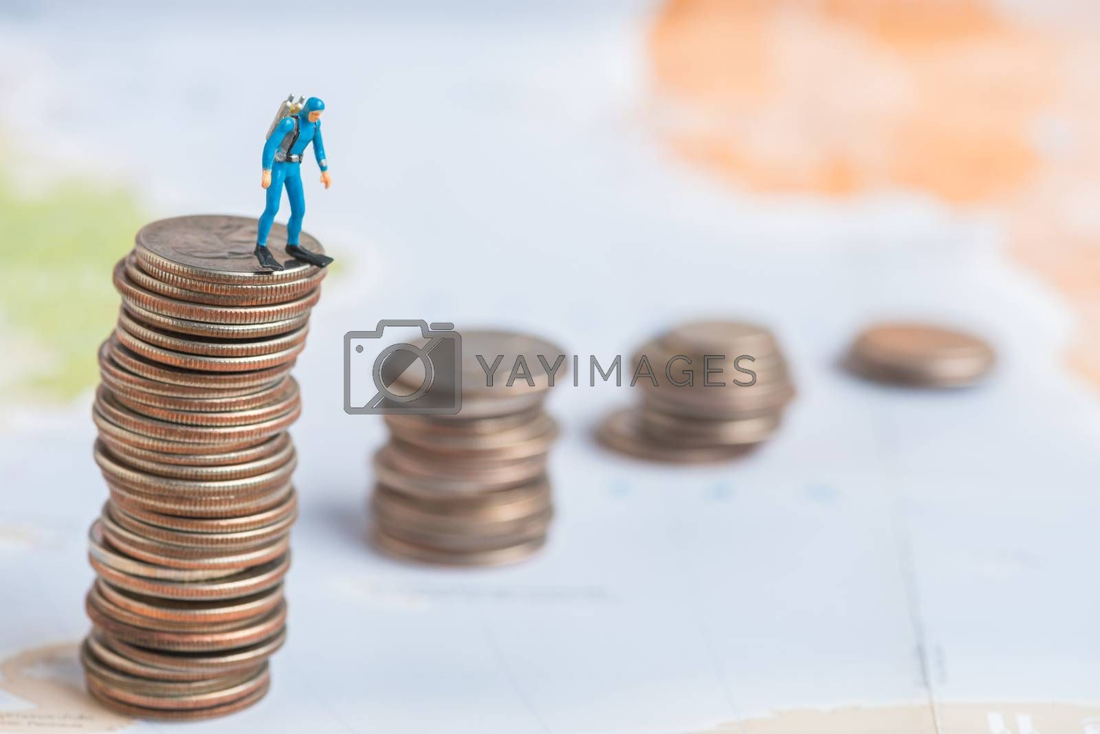 scuba diver miniature man standing on stack of coins with world map background.
