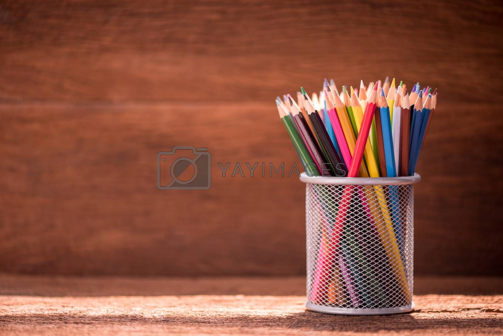 pencil box on wooden table by Lerttanapunyaporn