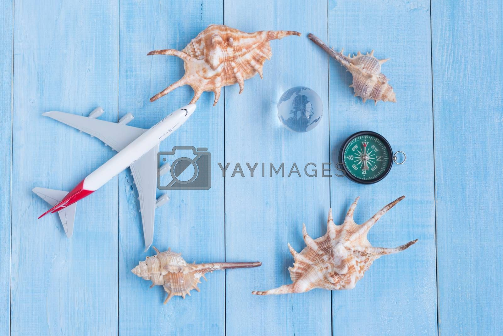 top view of travel accessories on light blue wood plank floor for summer vacation time