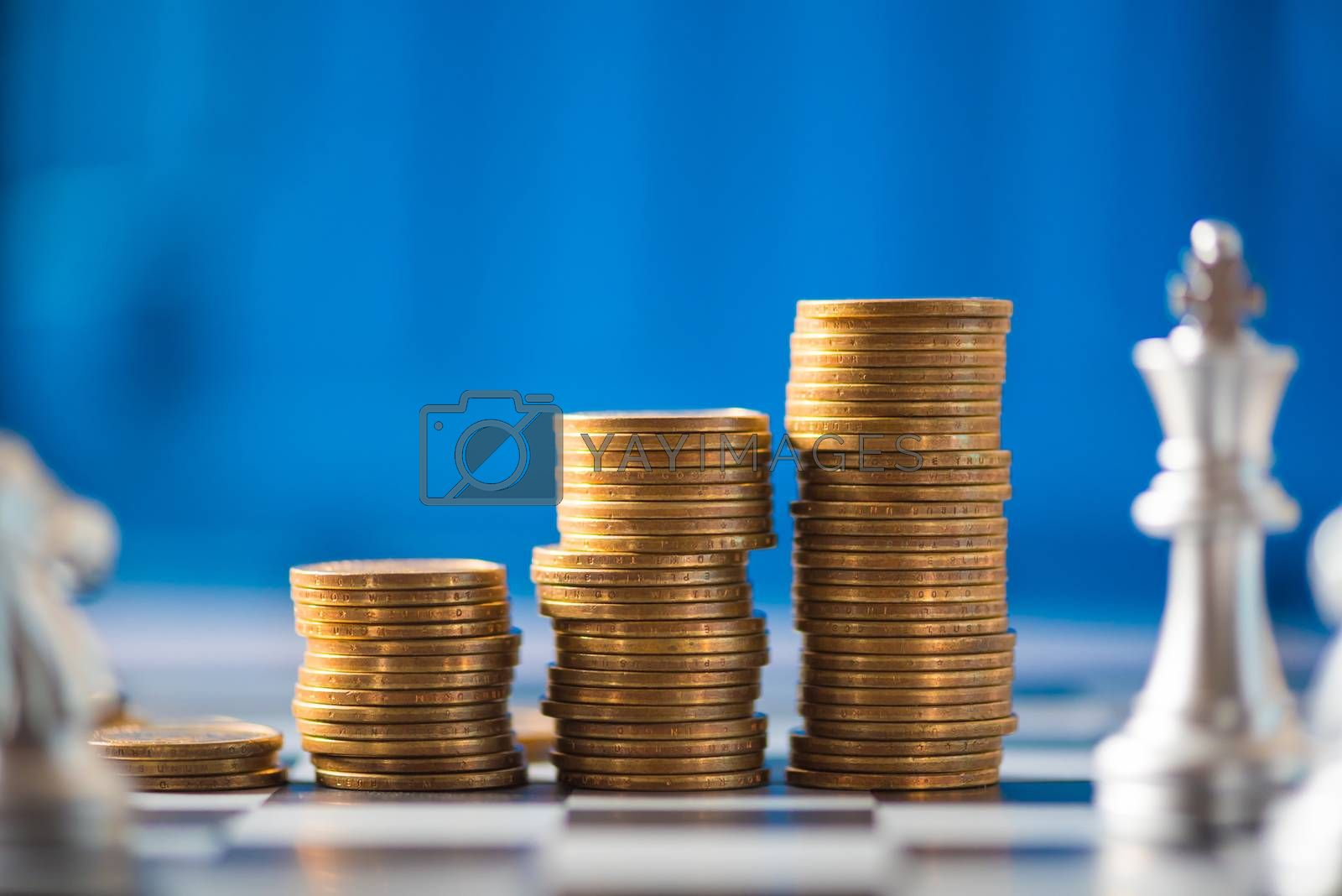 stack of coins on a chessboard, business strategy concept