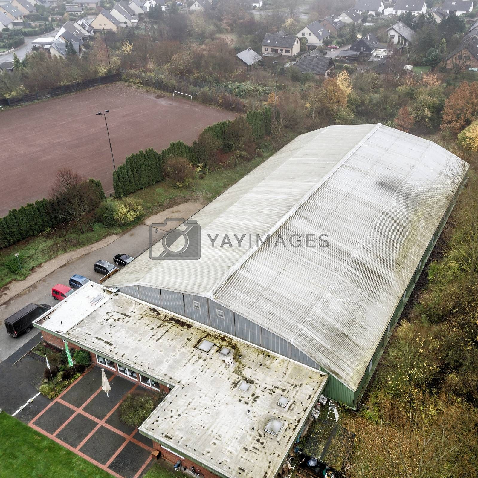 Aerial photo of an old ugly tennis hall with a residential area  by geogif