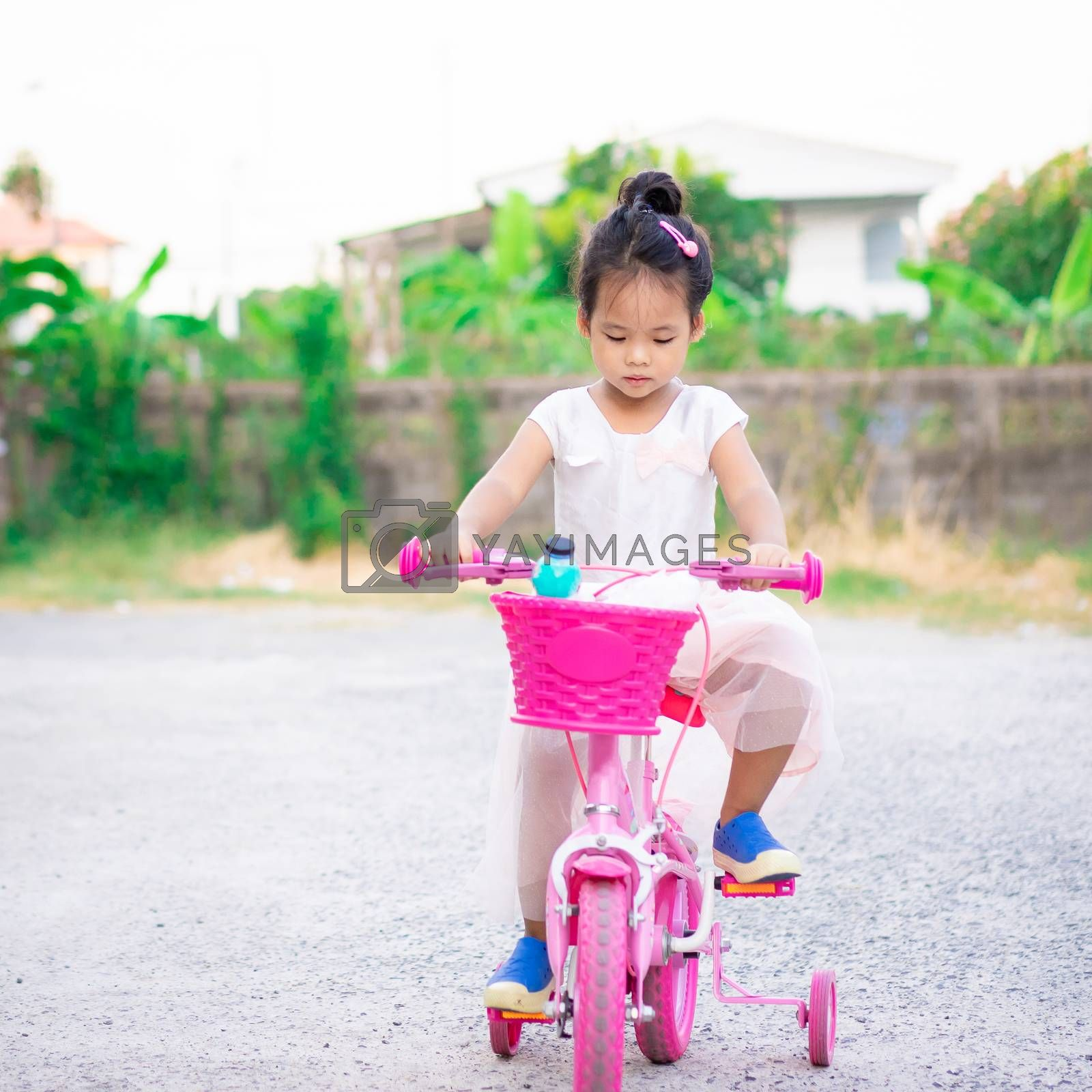 Cute little asian girl riding a bicycle to exercise on the street, kids sport and active lifestyle