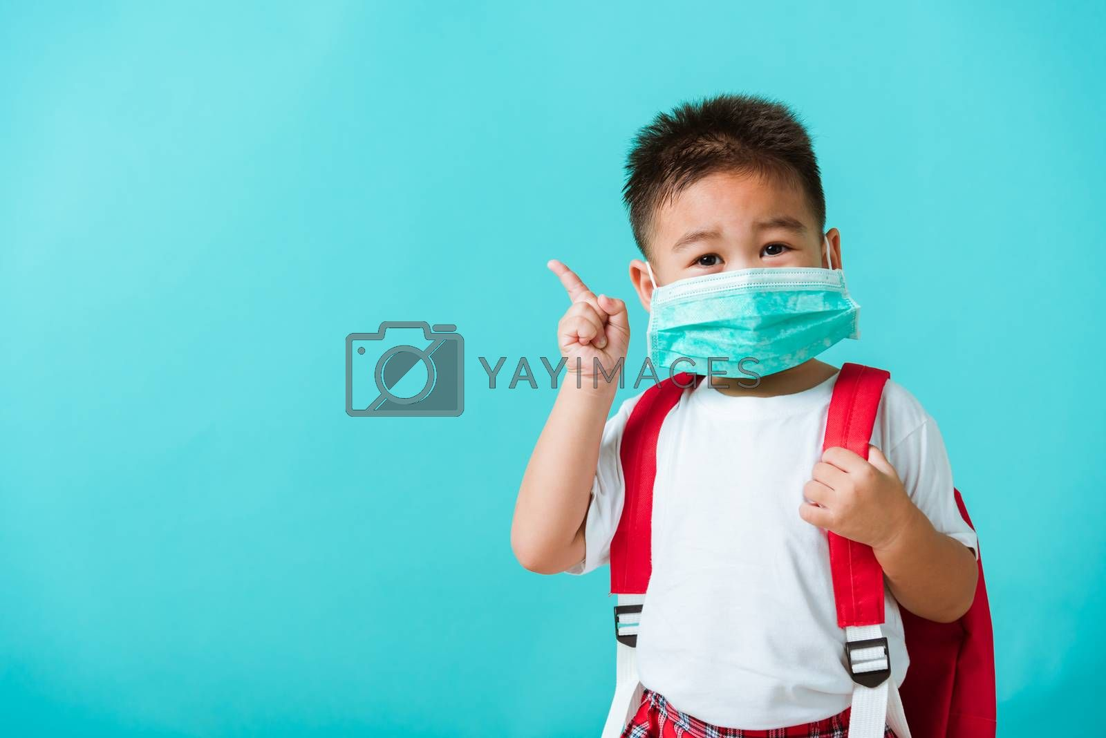 Back to school coronavirus Covid-19 education. Portrait Asian cute little child boy kindergarten wear face mask protective and school bag pointing finger to side, studio shot isolated blue background