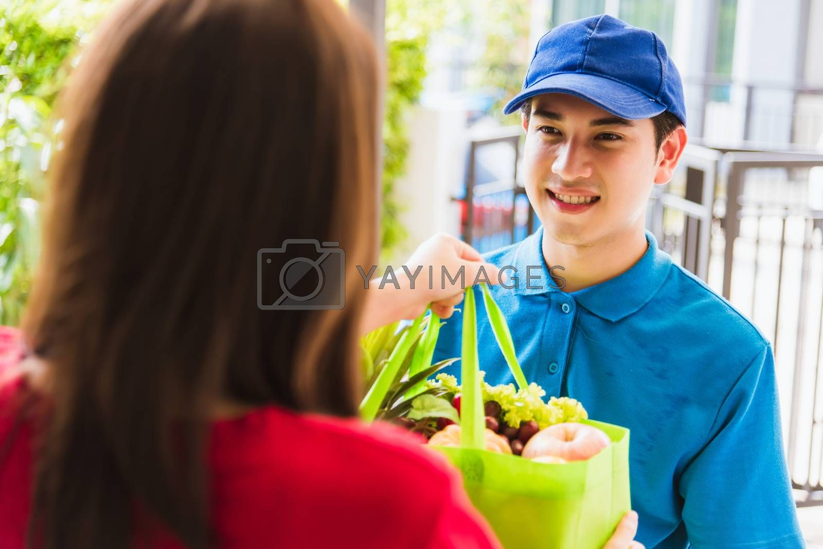 Asian young delivery man in uniform making grocery service giving fresh vegetables and fruits and food in green cloth bag to woman customer at door house after pandemic coronavirus, Back to new normal