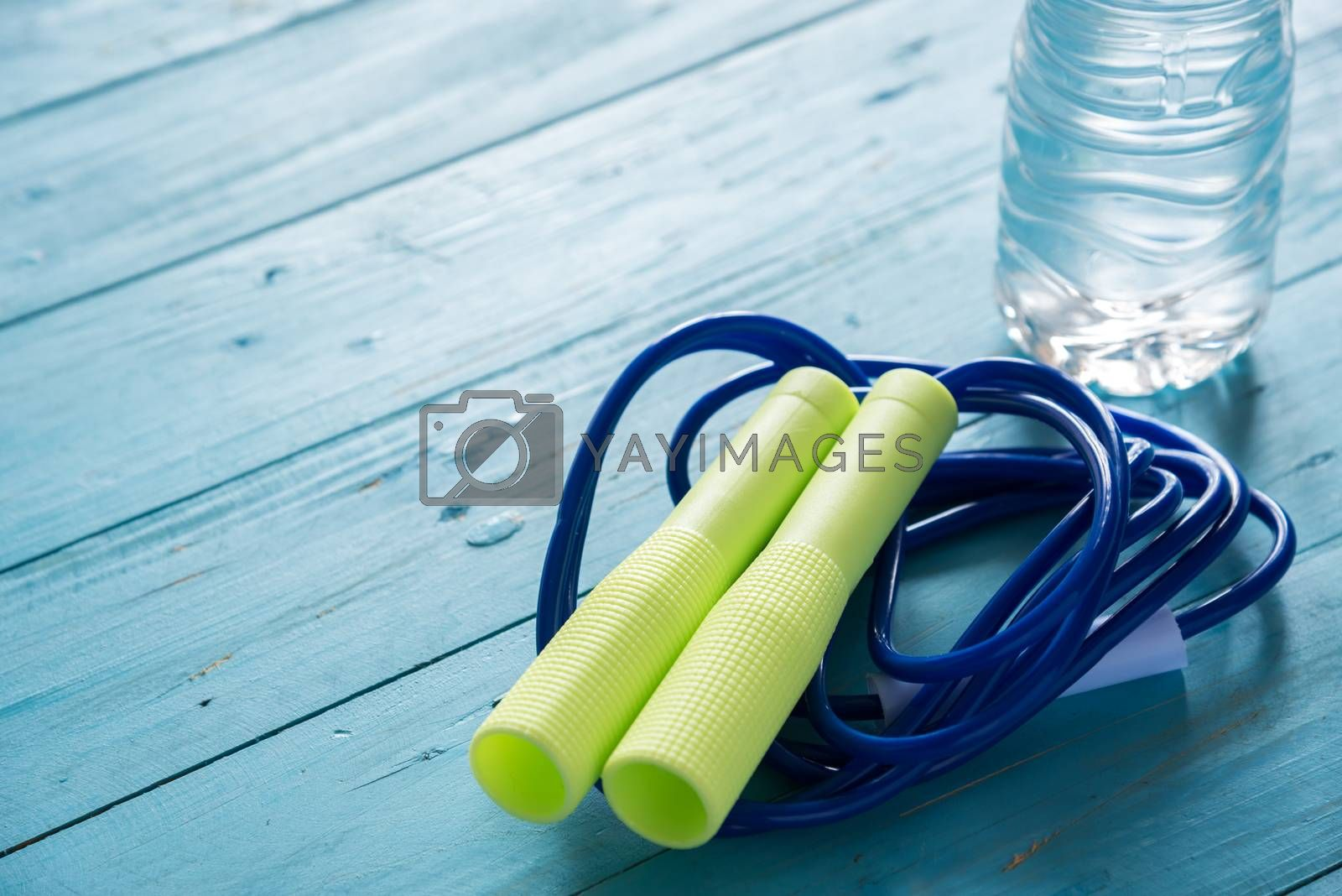 skipping rope and water bottle for an exercise on wood table by Lerttanapunyaporn