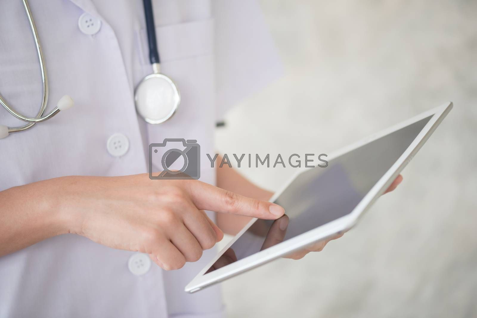 woman doctor finger touch on tablet screen by Lerttanapunyaporn
