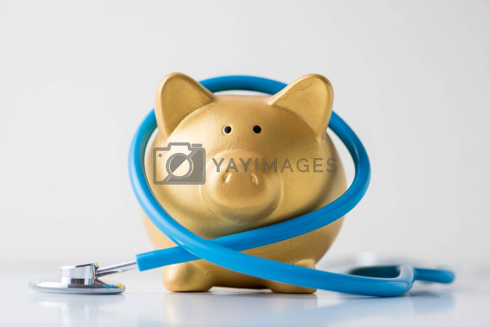 piggy bank with stethoscope on white background by Lerttanapunyaporn