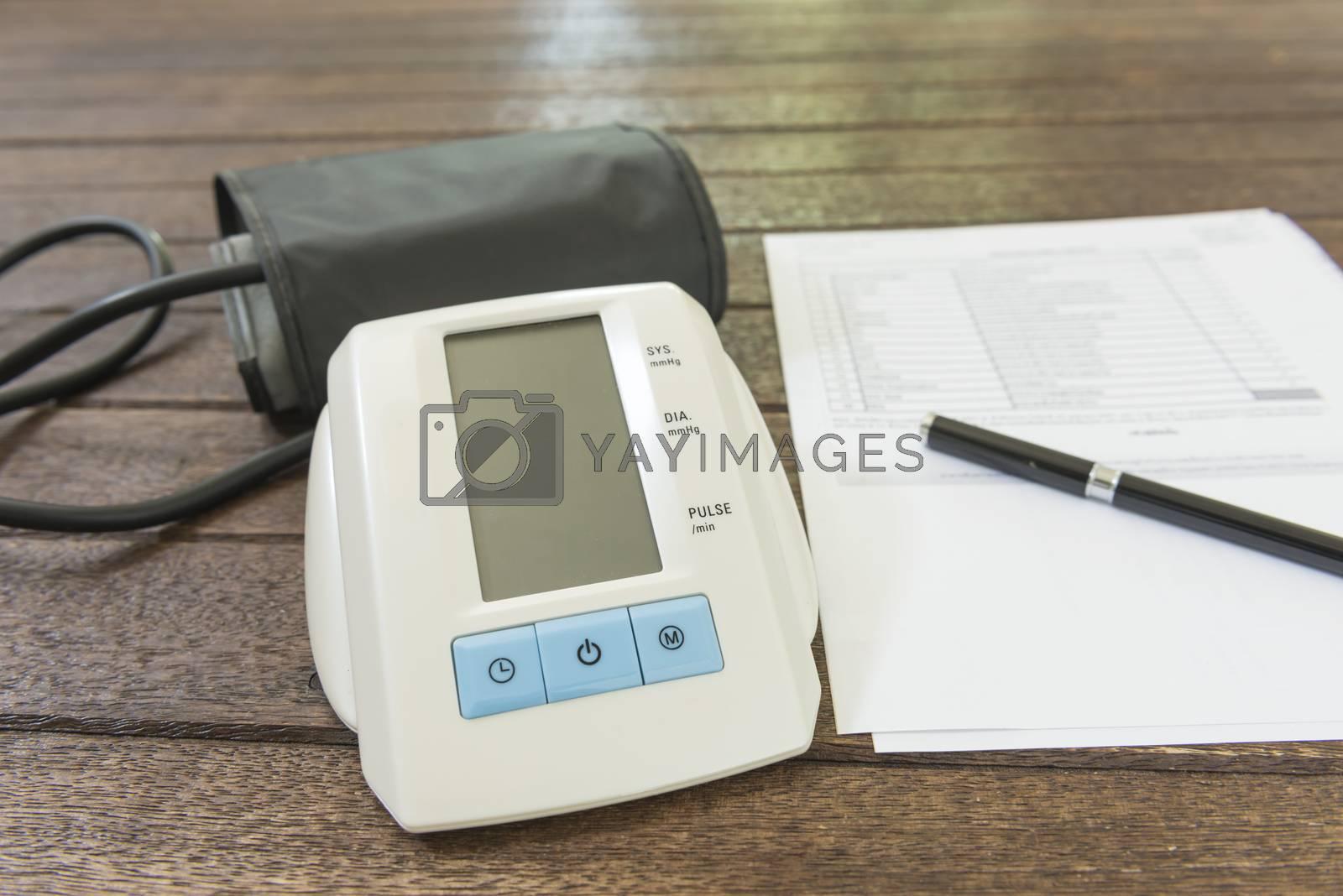 Digital blood pressure monitor on a wood table.