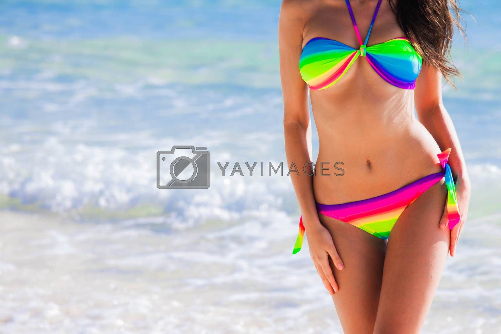 Woman with perfect body in rainbow bikini over blue sea background