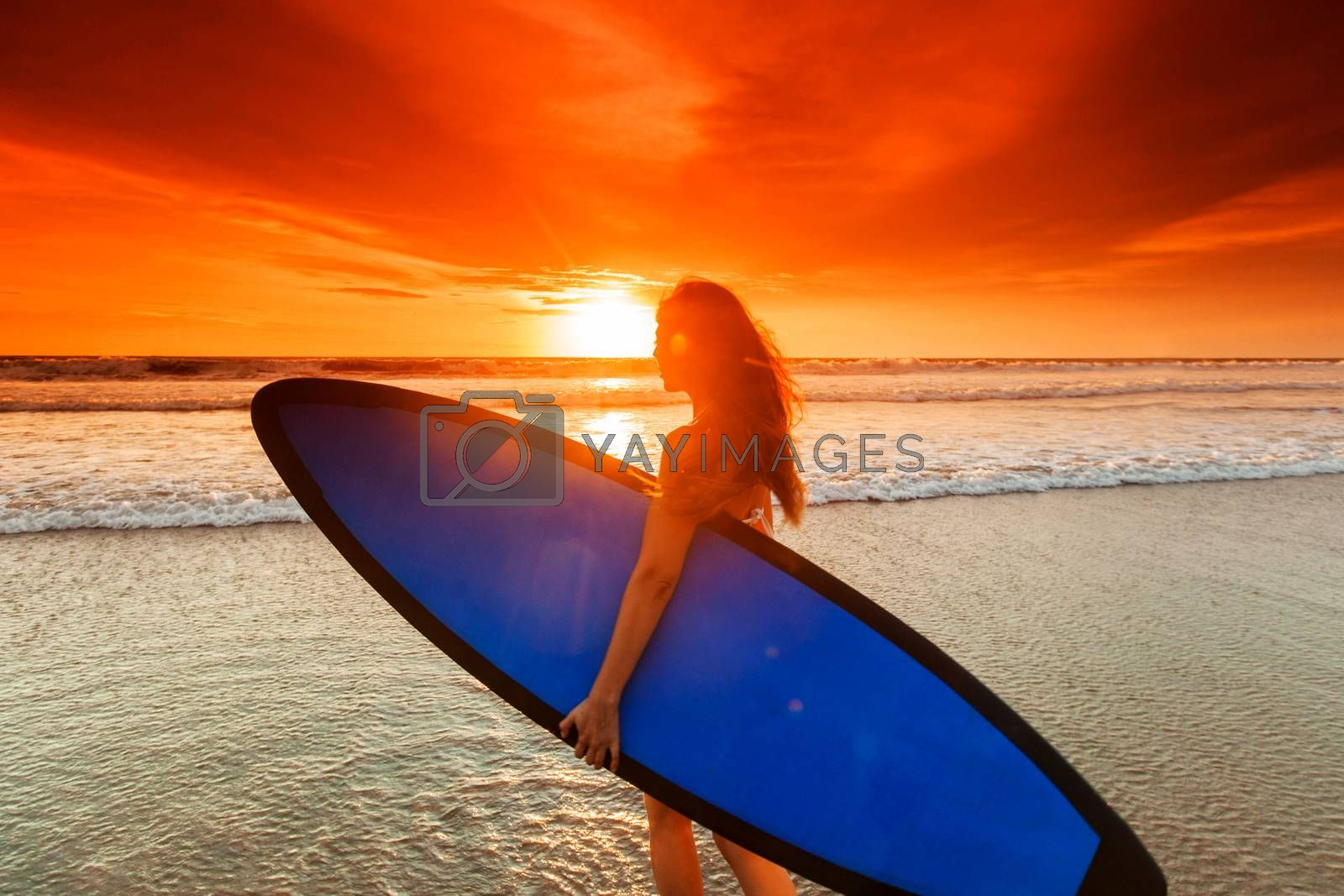 Beautiful mixed race woman on tropical beach holding surfboard at sunset