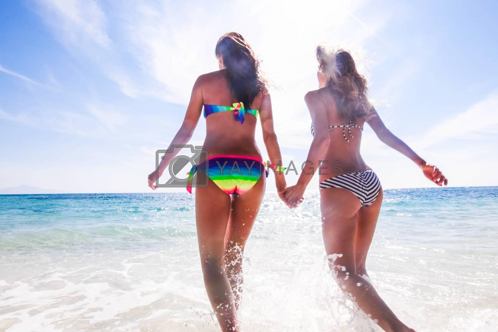 Beautiful fit women in bikni run on tropical beach to sea waves rear view