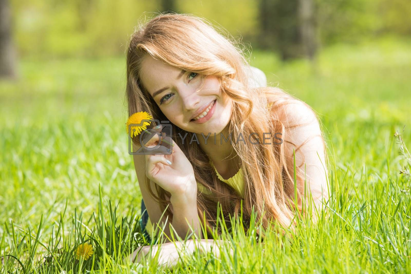 Happy smiling young woman laying on the green grass holding yellow dandelion flower