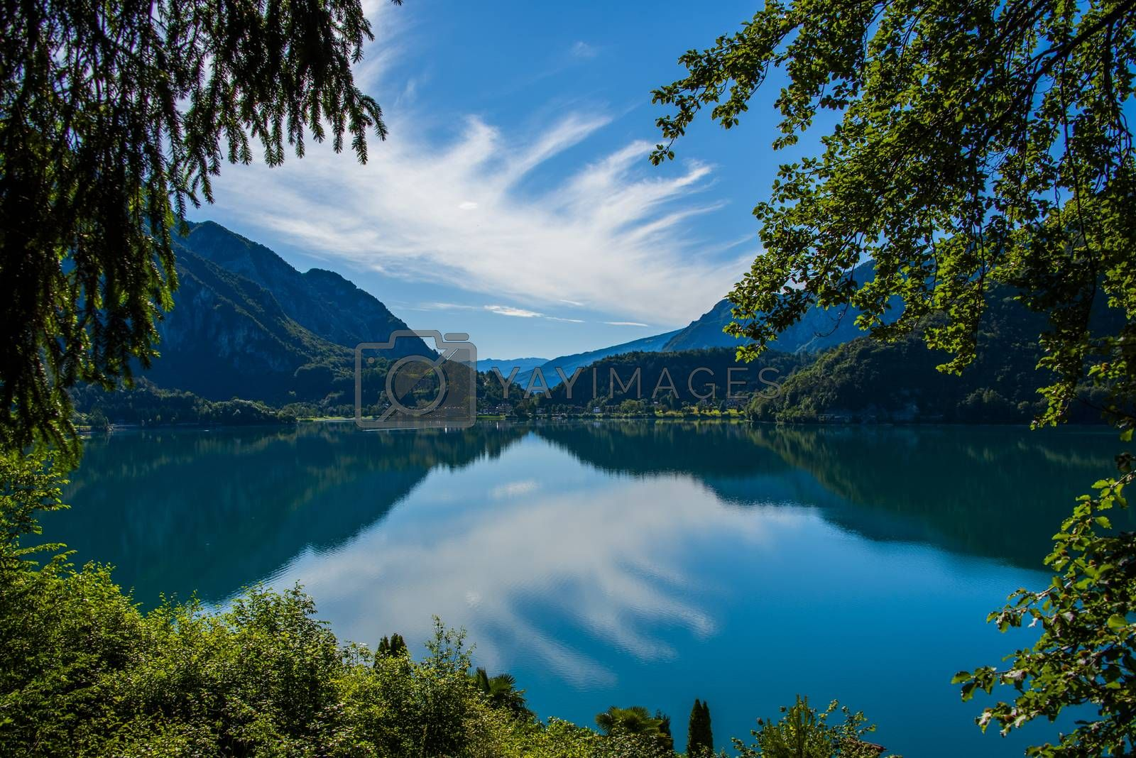 beautiful view of Lake Ledro with pontoon boats, villages and the daily life of a mountain lake in the Alps in Trento, Italy