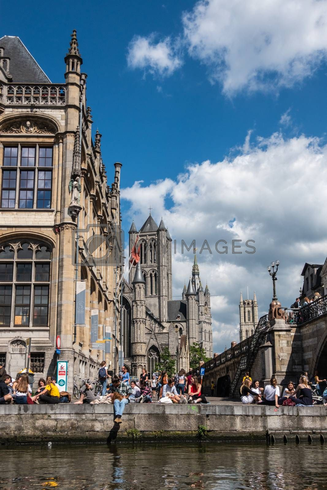 Gent, Flanders, Belgium -  June 21, 2019: School children and students enjoying sun sitting on quay of Leie River and Graslei. Three towers of city in back.. Blue sky and clouds.