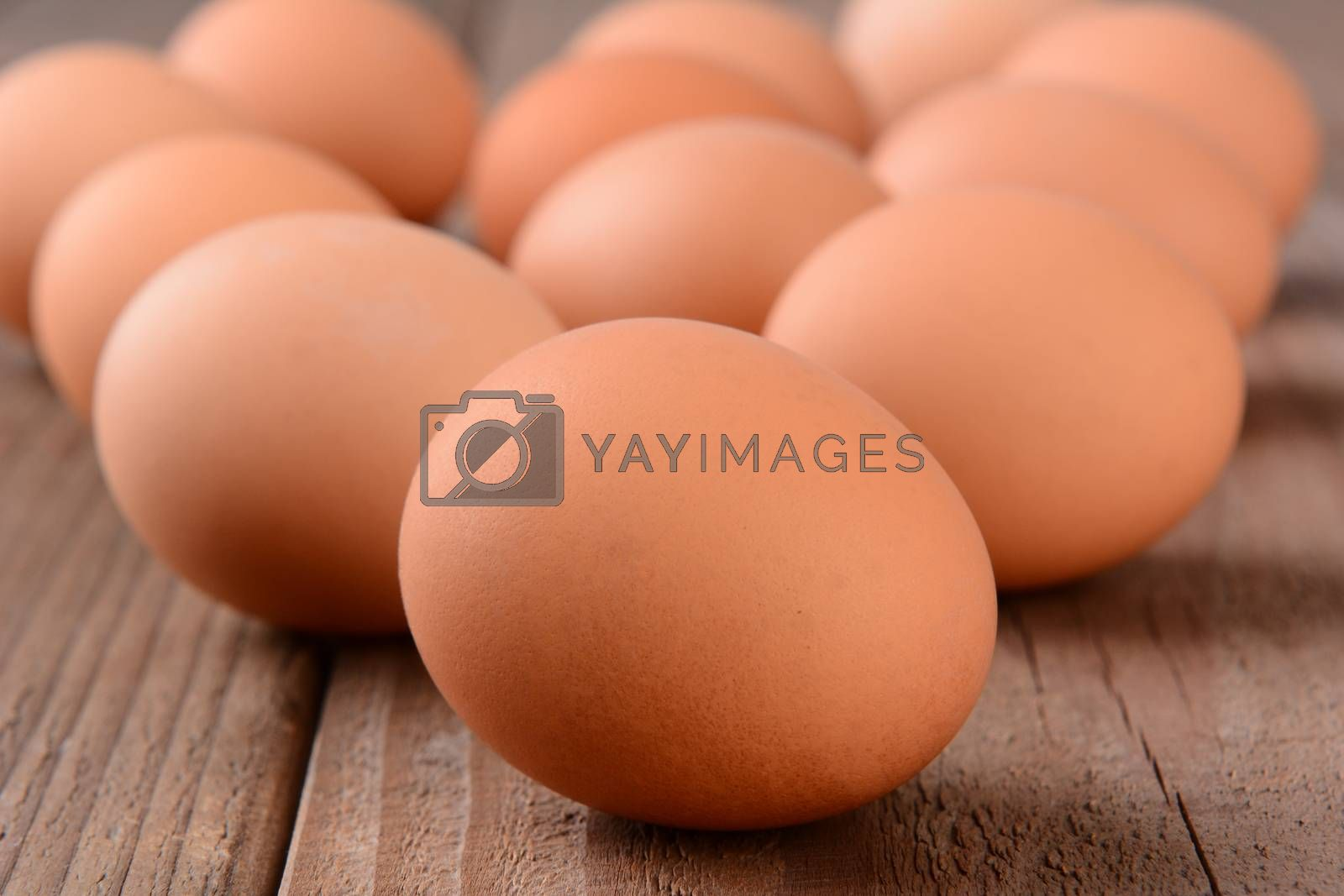 Closeup of a group of brown eggs on a rustic wooden table. Horizontal format with shallow depth of field.