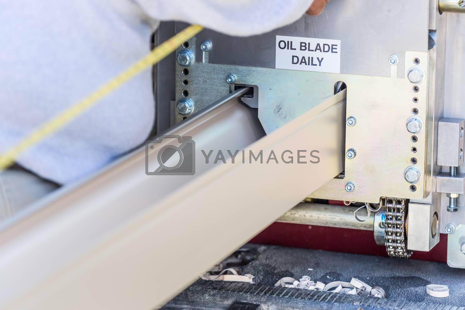 Worker Measuring Rain Gutter Processing Through Seamless Shaping Machine.