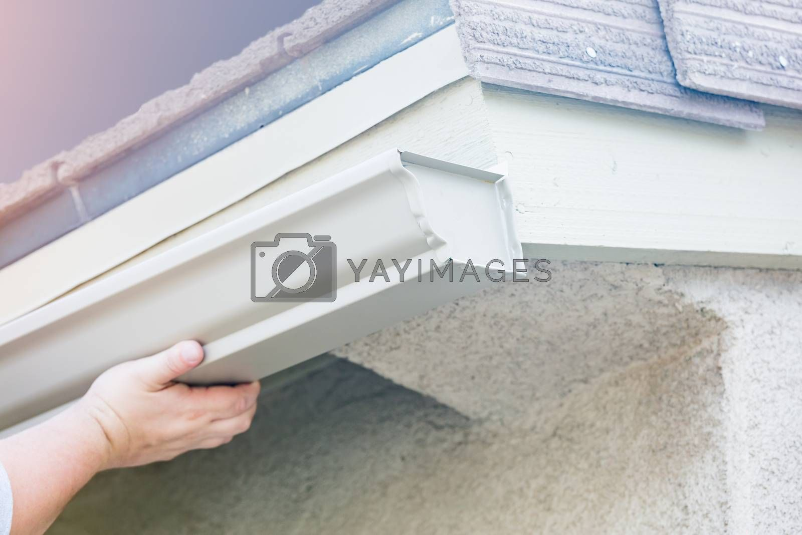 Worker Attaching Aluminum Rain Gutter to Fascia of House.