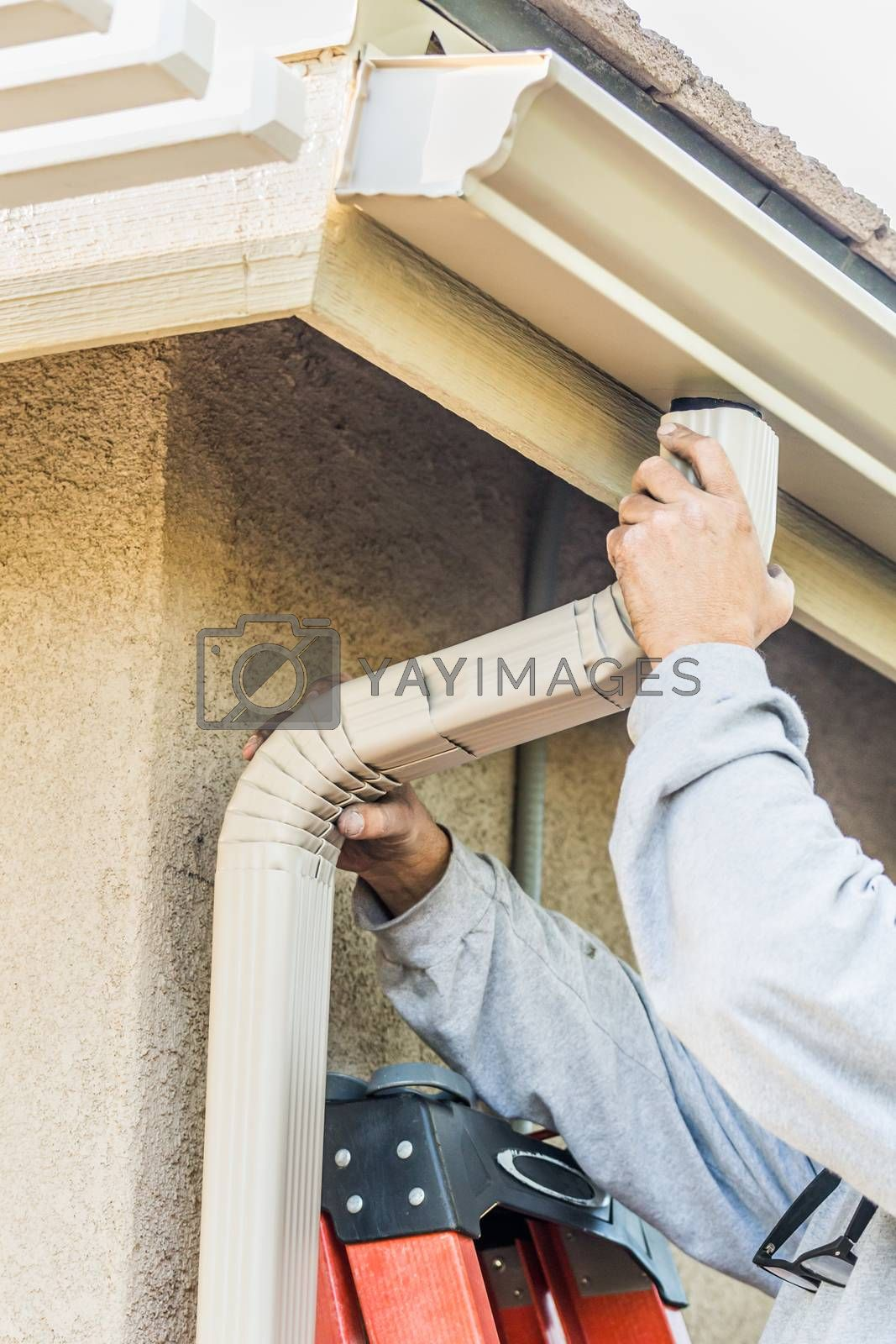 Worker Attaching Aluminum Rain Gutter and Down Spout to Fascia of House. by Feverpitched