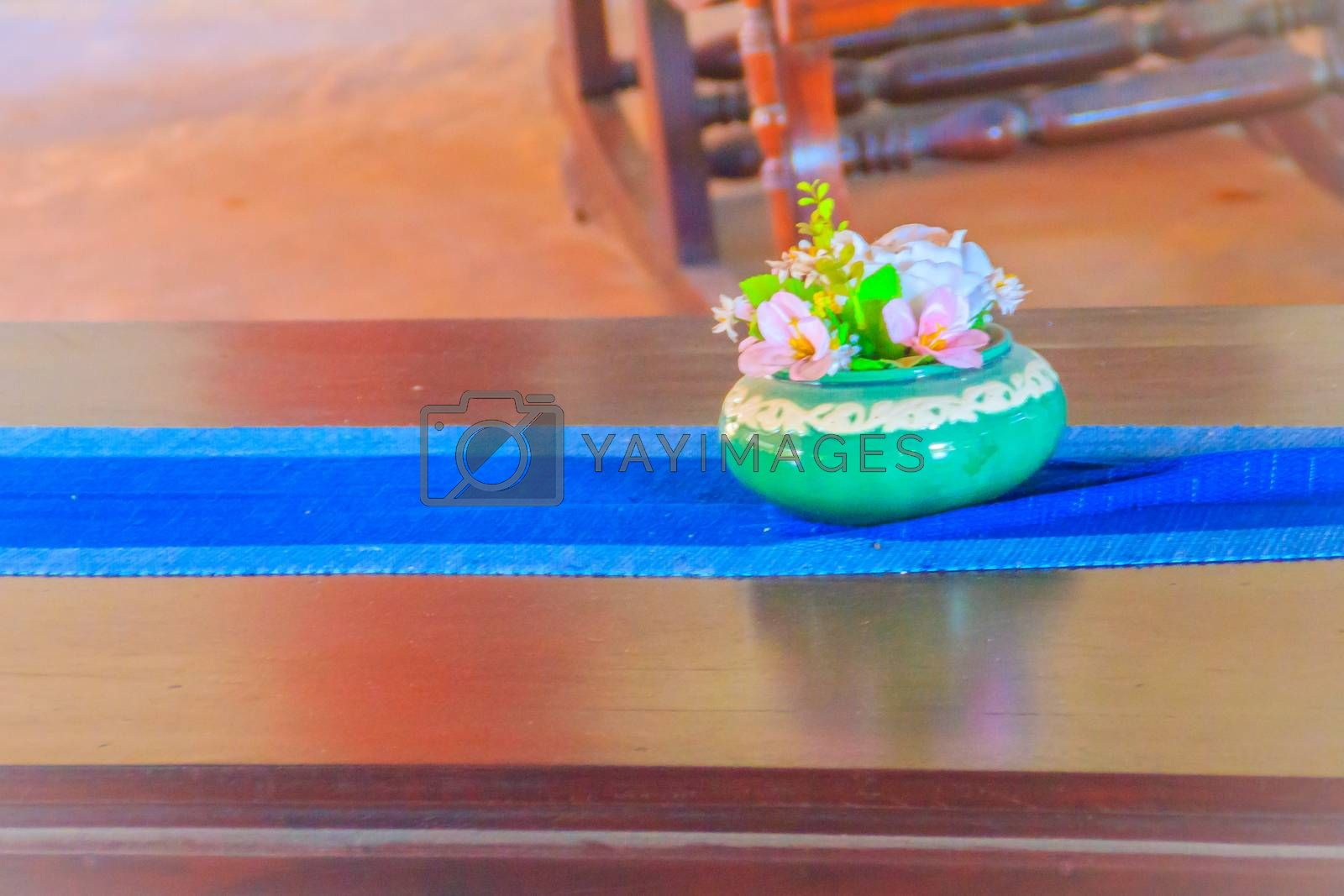 Beautiful blue porcelain vase with pink flowers on the wooden brown table.