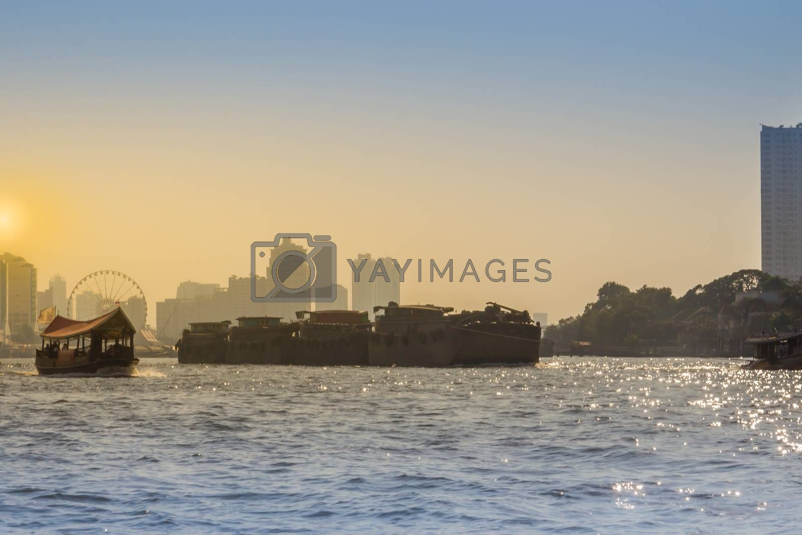 Riverfront view of tug boat drags cargo barge on Chao Phraya river in Bangkok, Thailand.