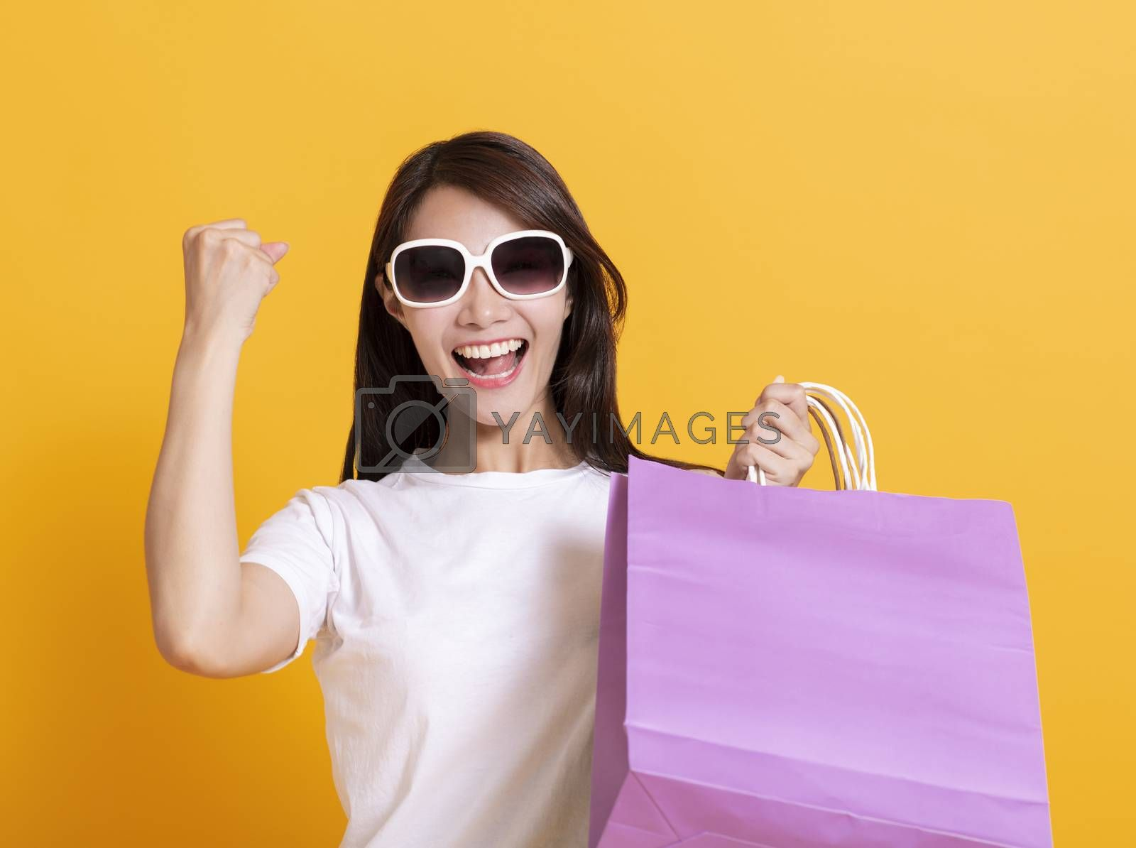 young woman in sunglasses and showing the shopping bags
