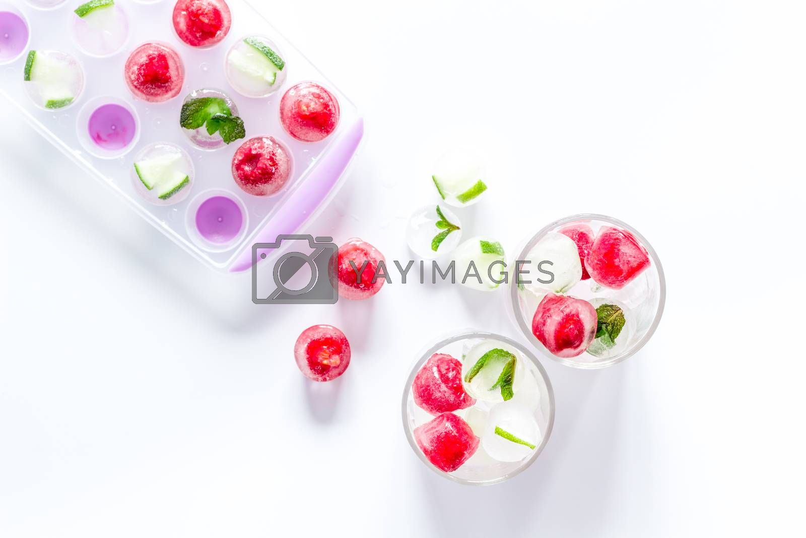 Raspberry and lime in ice cubes top view flat lay.