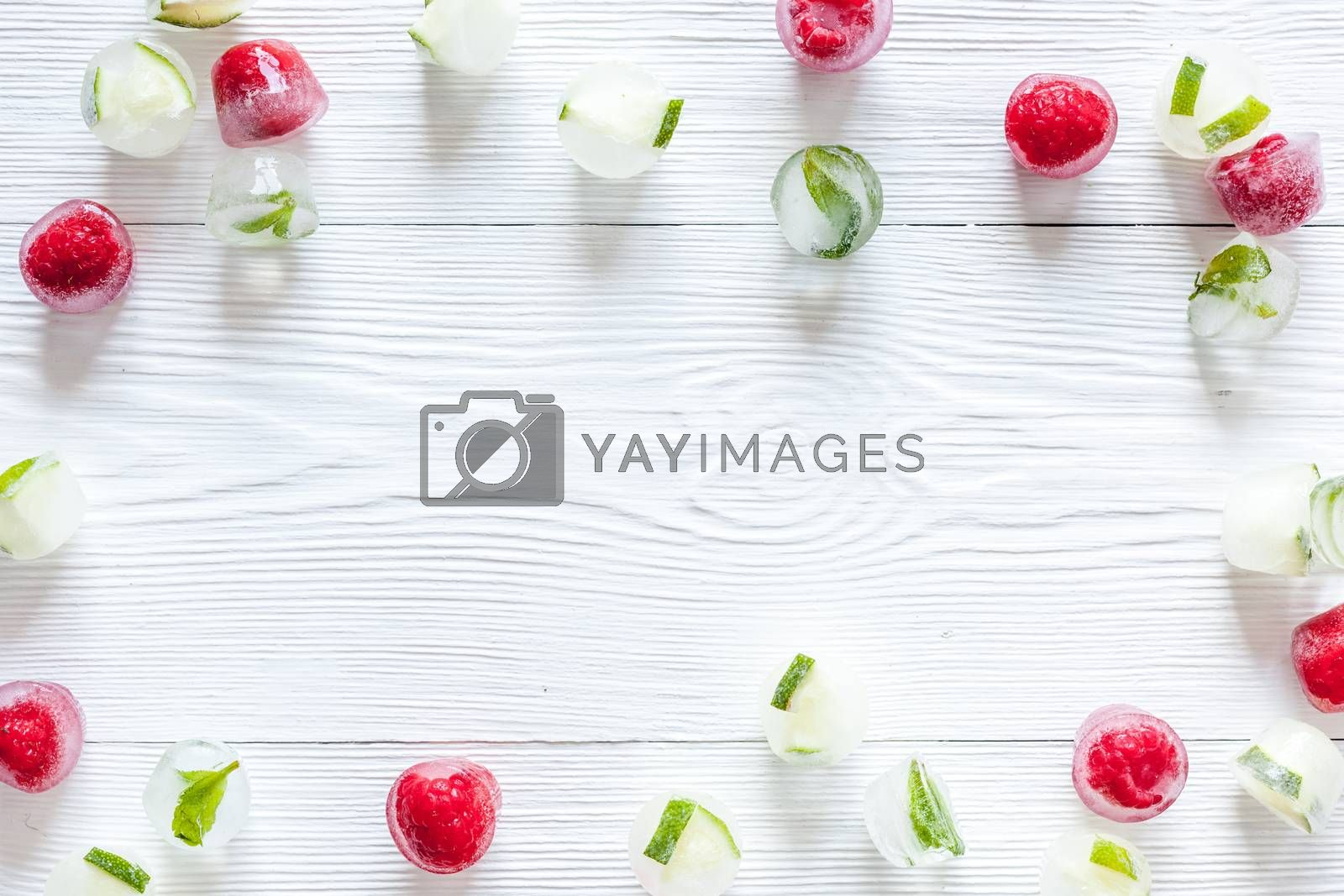 Ice cubes with berries and mint top view copy space.