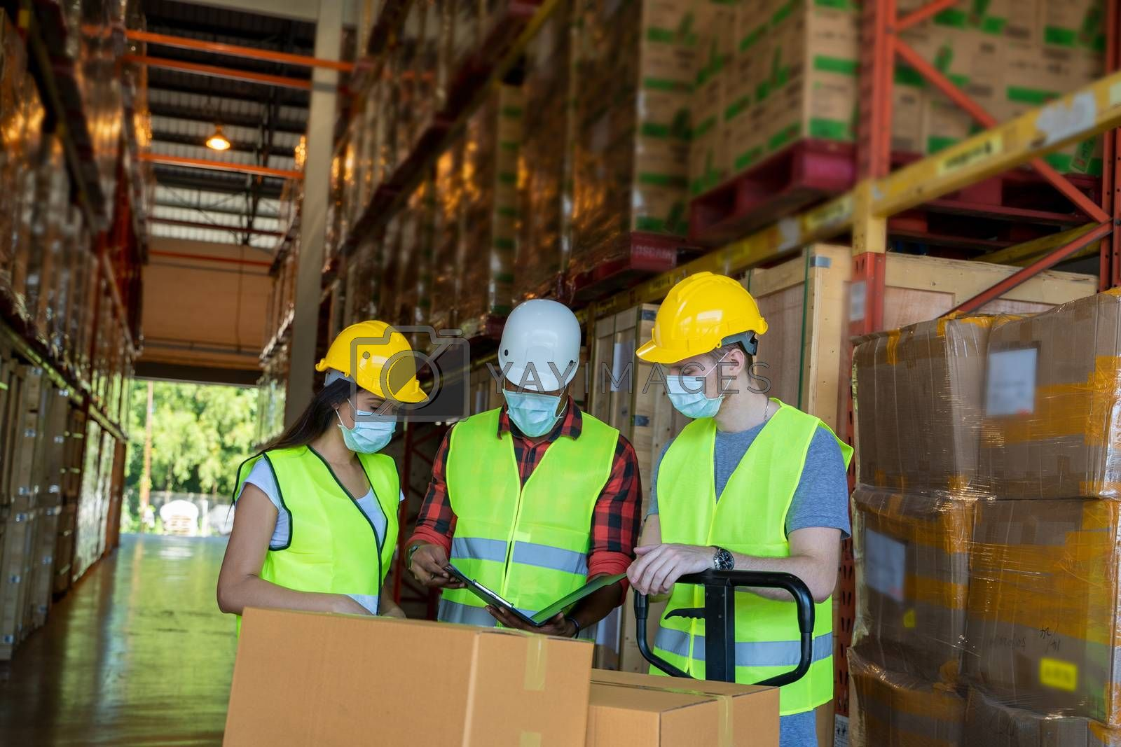 Warehouse workers wearing protective mask to Protect Against Covid-19 with clipboard during work in a warehouse.