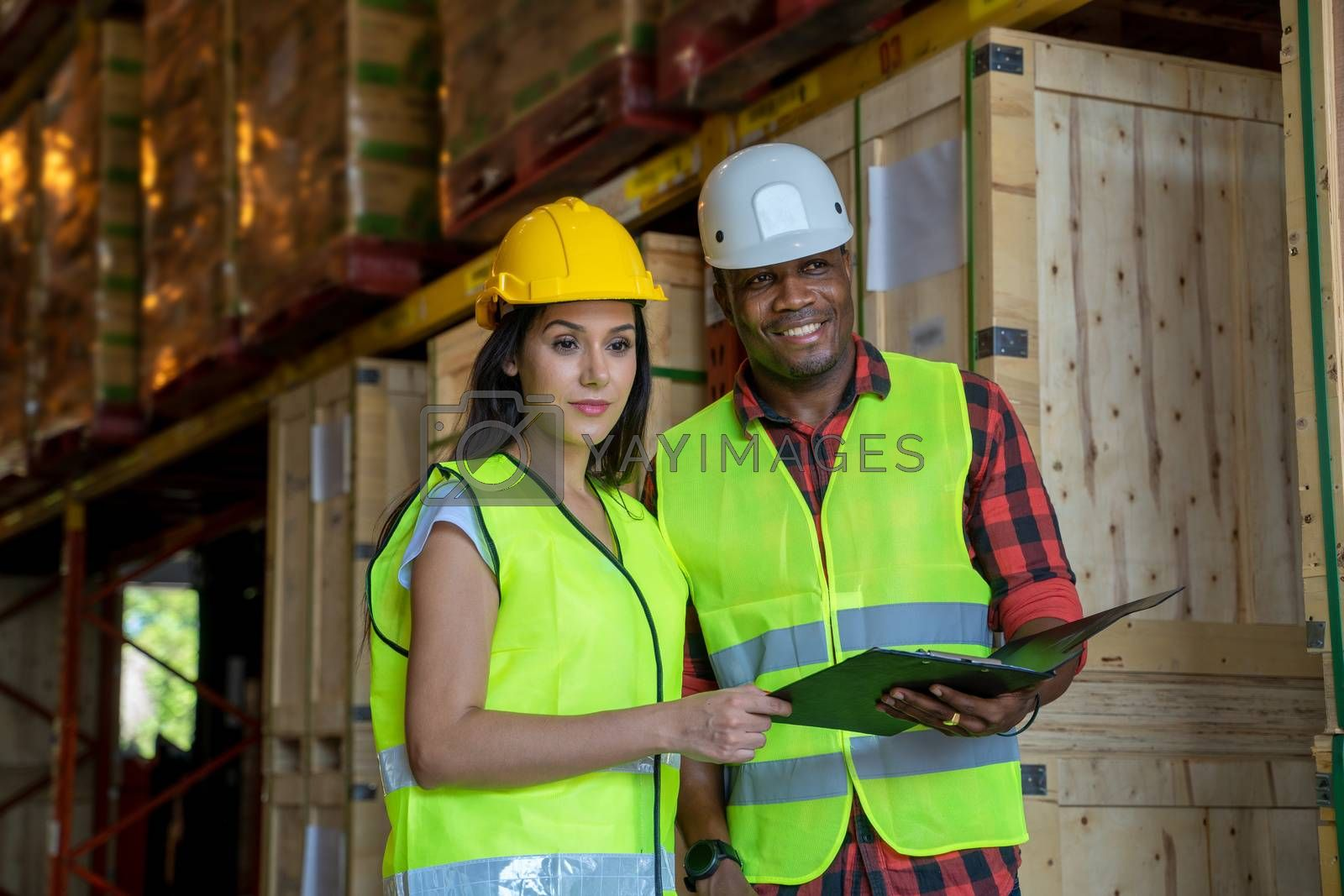 African American worker working with clipboards at warehouse.