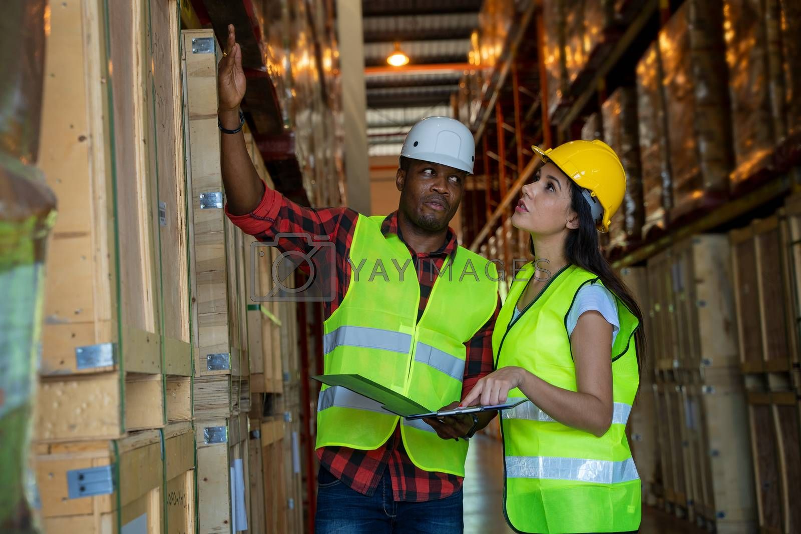 Warehouse manager and warehouse worker wearing helmet  with clipboard checking products about delivery schedule in industrial storage room.