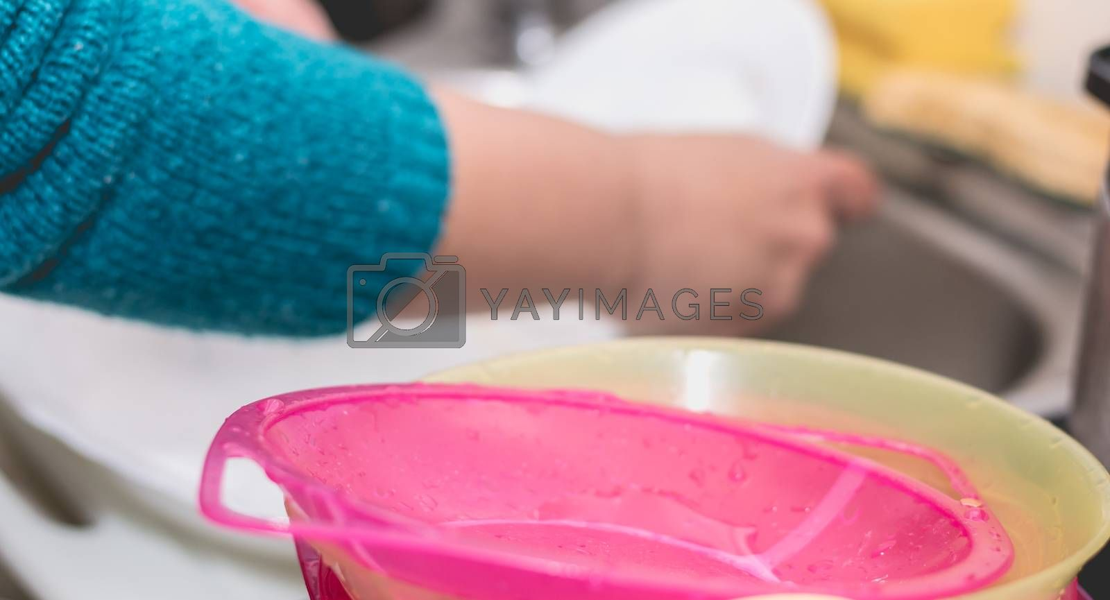 Close-up of the hand of a woman doing dishes