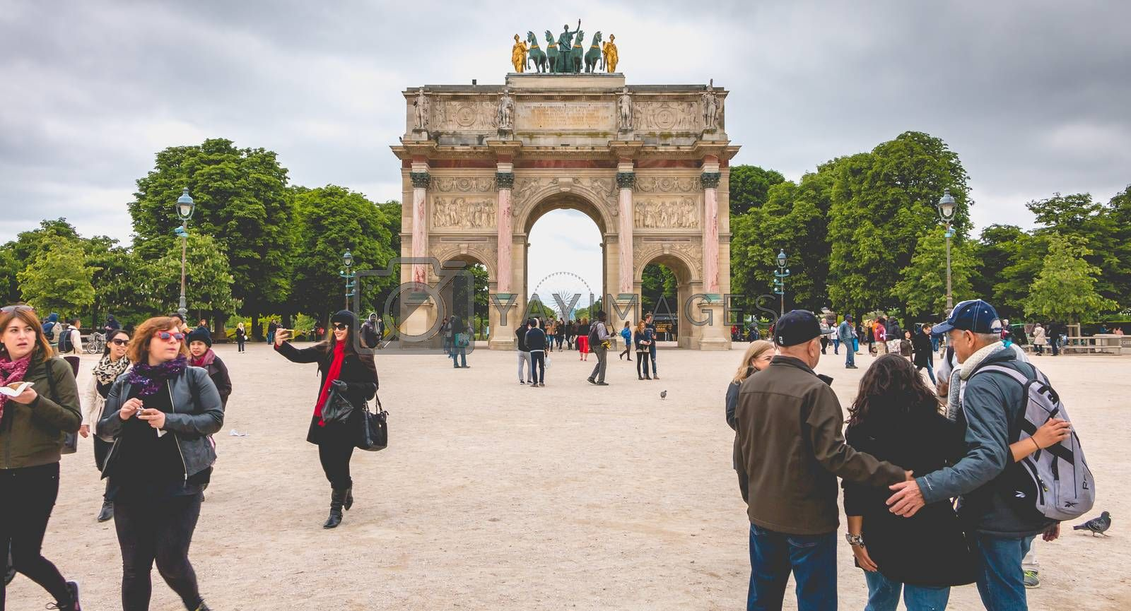 Paris, France - May 08, 2017 : In the garden of the tuileries, tourists walk before the triumphal arch of the carousel. The arch was built from 1806 to 1808 to commemorate the Napoleon's military victories