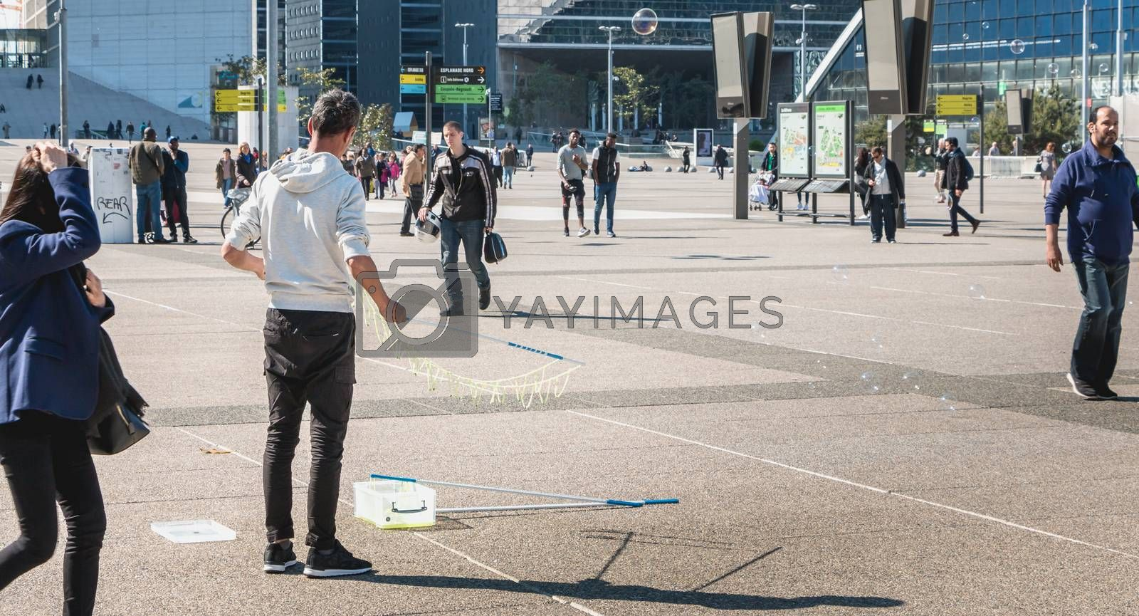 Nanterre, France - May 09, 2017 :  A man, watched by passers-by, makes giant bubbles in the middle of the central square of defense, the great modern business district of Paris, France