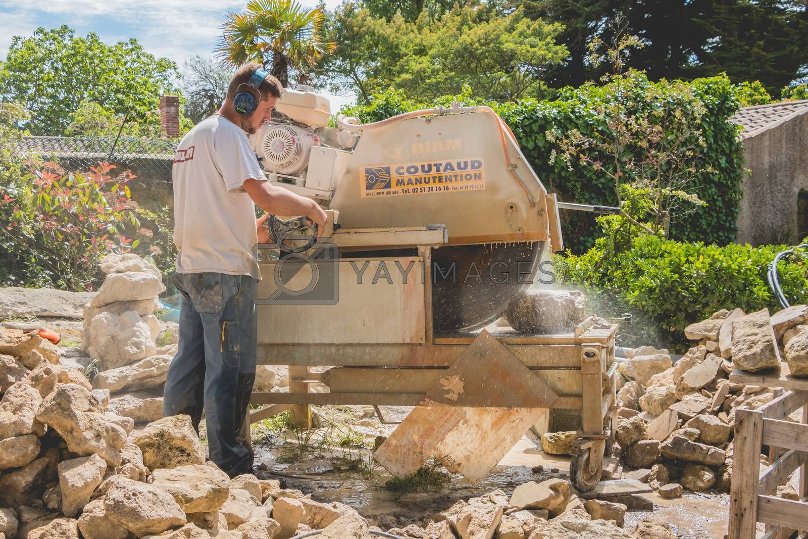 Noirmoutier, France - May 16, 2017 :  a man cutting a stone with a water saw on a renovation site