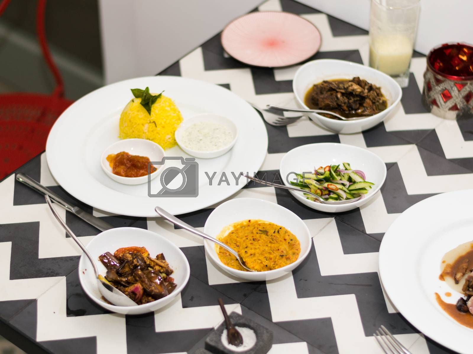 Traditional Sri Lankan curry with saffron rice, lentils, spices and greens, served in a white dish