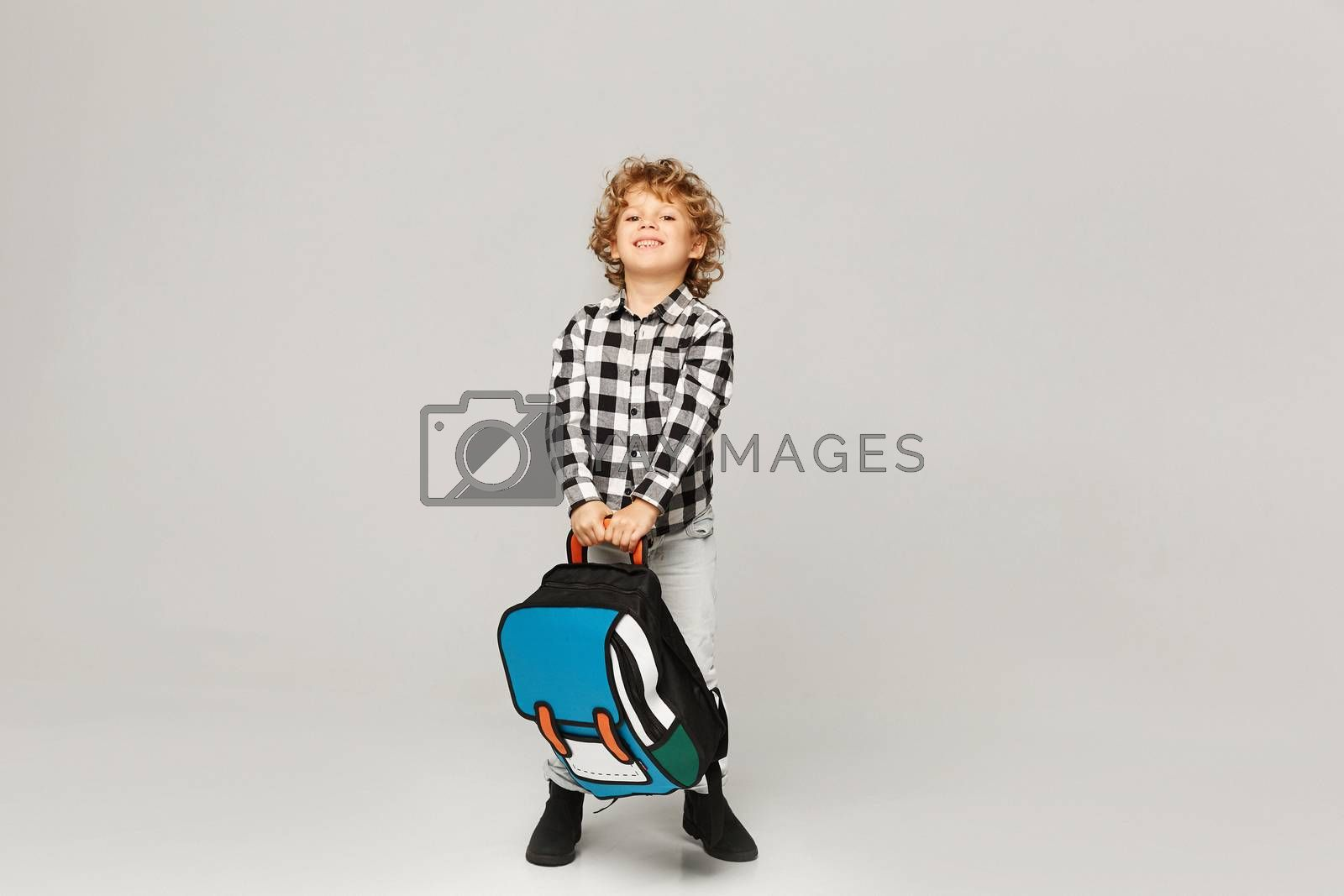 Back to school. A funny little boy from elementary school posing with a backpack over white background, isolated by Ina