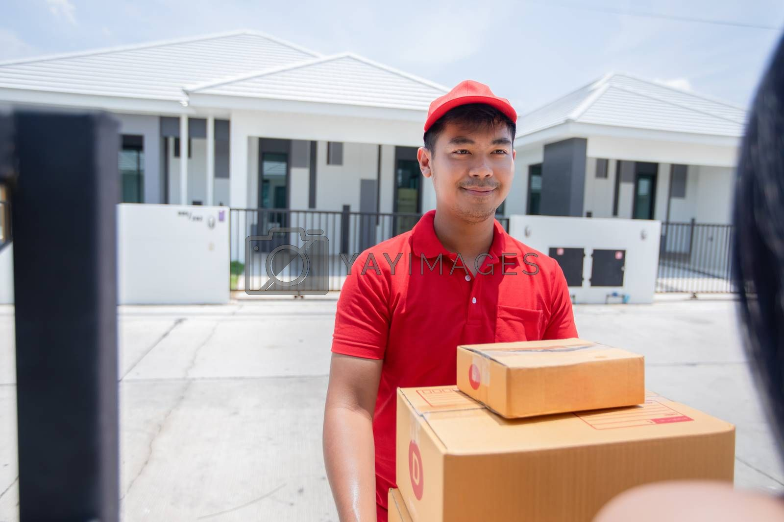 Asian delivery servicemen wearing a red uniform with a red cap and handling cardboard boxes to give to the female customer in front of the house. Online shopping and Express delivery